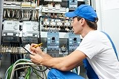 person taking notes of a commercial electrical unit